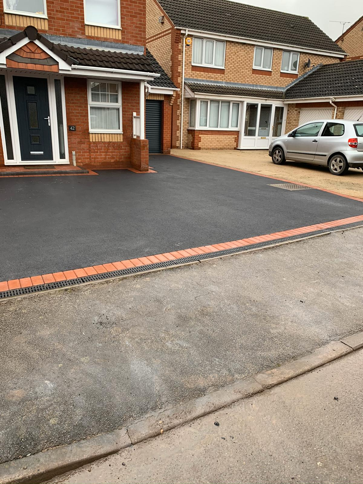 Newly laid tarmac driveway in coventry include red brick edges and dropped kerb