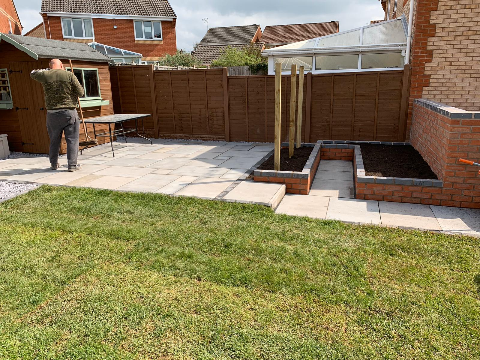 Newly laid patio area including screen, walls and turf