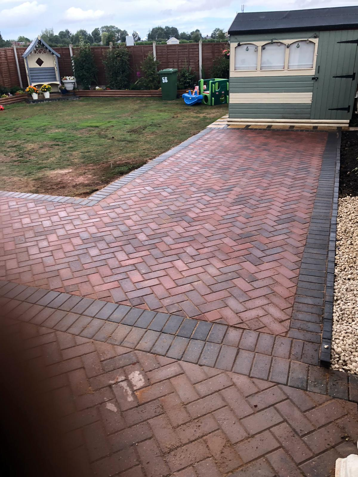 Block paved pathway in back garden using red and black bricks